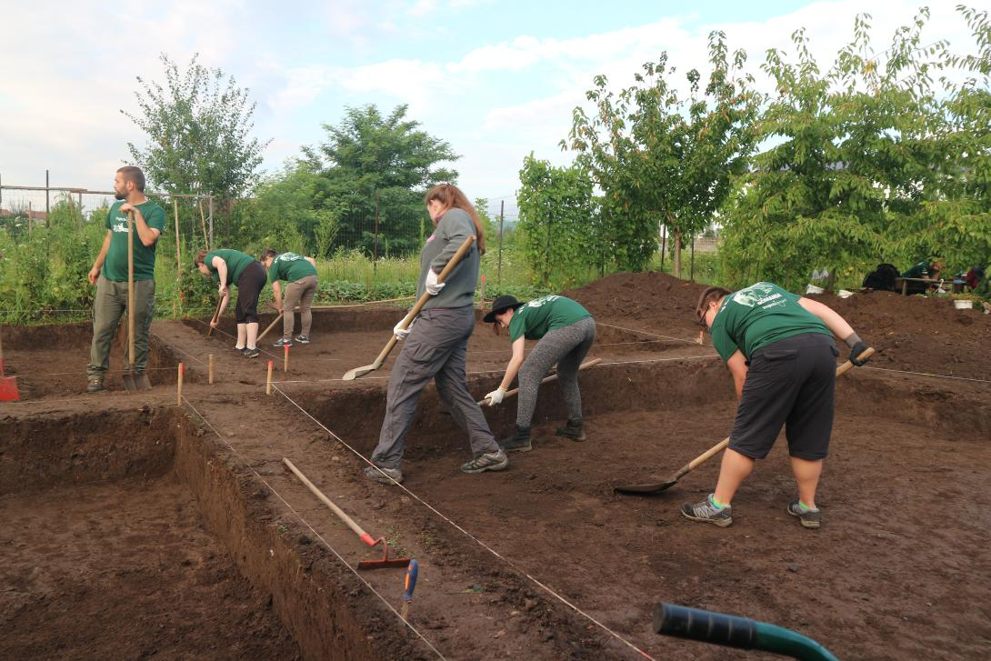 Archaeology volunteers in Romania digging at an excavation site
